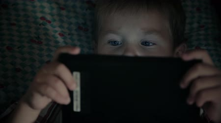 Kid face looking at tablet computer at night Wideo