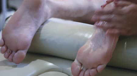 Massagist making foot massage for man in the clinic