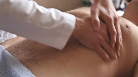 Massagist making abdominal massage for man in the clinic