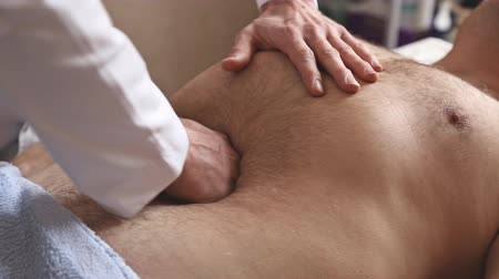 břišní : Massagist making abdominal massage for man in the clinic