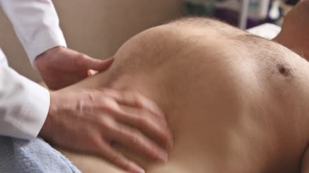 манипуляция : Massagist making abdominal massage for man in the clinic