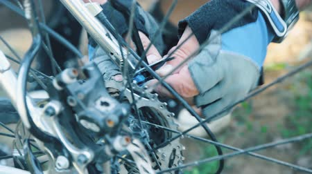 Male cyclist repairing bicycle at countryside road. Close-up. Wideo