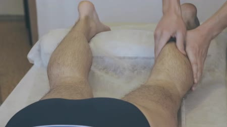 манипуляция : Massagist making leg massage for man in the clinic Стоковые видеозаписи