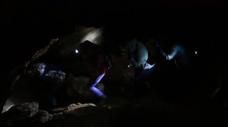 Group of young people walking one by one through the cave Wideo