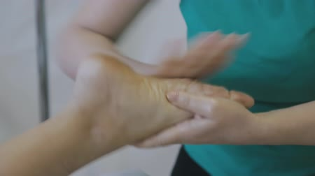 Female physiotherapist making foot massage for woman in the clinic
