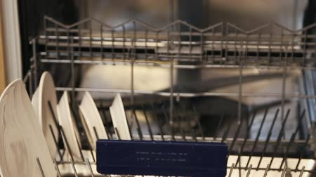 Female hands putting big and small white plates in the dishwasher. Wideo