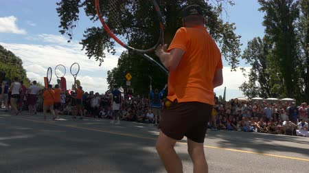 participante : Mature male walking big tennis racquet