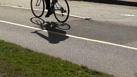 ciclismo : Bicyclist shadow moving on asphalt slow motion