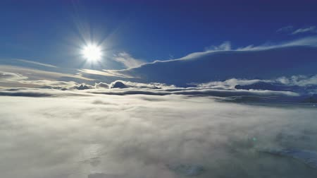 Antarctica sun, fog. Aerial view drone flight 4k. Antarctic overview bright white sun above dense surface smog covering the ocean water and mounts. Amazing winter panorama. Polar scenery.
