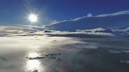 glare : 4k Antarctica landscape. Aerial view drone flight. Sun track of white bright polar sun over the ocean covered by light fog. Ice and snow covered surface of Antarctic continent. Panoramic overview.