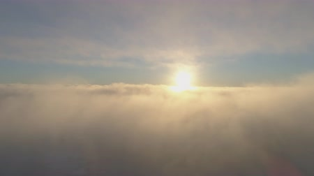 Sunset over moving fog. Antarctica aerial drone view flight. Amazing time lapse overview scene the bright light orange sun over the fast flowing fluffy clouds above the Antarctic continent. 4k footage.