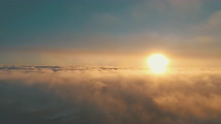 Sunset, fog. Antarctica aerial drone view flight. Breathtaking scene the bright orange sun over the fast moving fog over the Antarctic continent surface. Fluffy clouds. Timelapse shot. 4k footage.