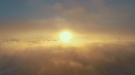 Sunset, fog clouds. Aerial drone flight view. Epic panoramic overview the bright orange sun above the fast moving surface fog covering Antarctic continent. Overwhelmed sky scape. 4k footage.