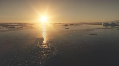 Antarctica ocean sunset light. Aerial drone view flight. Fast hyperlapse shot the bright orange sun over the ocean surface covered ice, snow pieces and icebergs. Flying over the water. Copter shot. 4k footage. Стоковые видеозаписи