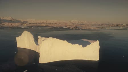 Close-up iceberg. Antarctica aerial drone view flight. Timelapse view from above sunlit iceberg with clear water pool in the ocean, next to the Antarctic continent shore with snow covered mountains. 4k footage.