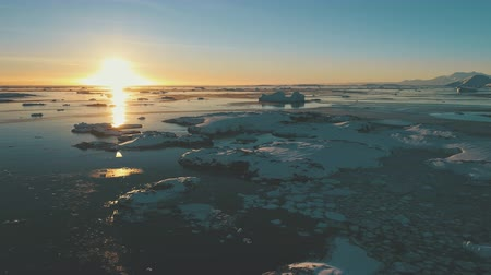 Sunset, ice ocean. Antarctica aerial drone view flight 4k. Epic, fast time lapse overview the sunset sky, above the ocean, with frozen ice pieces, icebergs. Orange sun track on water surface. Permafrost.