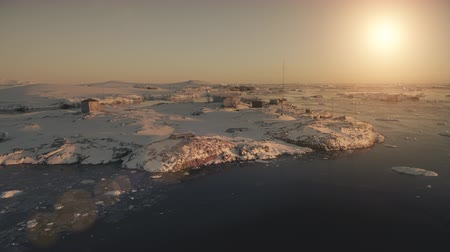 Antarctica Vernadsky base landscape. Aerial drone view flight 4k. Breathtaking panoramic overview Antarctic base among snow covered hills at the polar sunset. Timelapse shot. Settlement in harsh conditions.