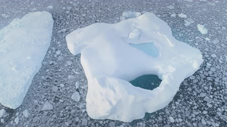 Aerial shot of close-up iceberg with pool. Antarctica zoom in drone flight. Ice mountain among polar ocean. Pieces of ice floating around frozen icebergs. Permafrost. Antarctic continent. 4k footage. Стоковые видеозаписи