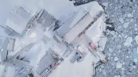 Aerial flight over Vernadsky station in Antarctica. Zoom drone view. Frozen polar ocean surrounding. Ice, snow covered land. Top down overview of Antarctic base. Zooming in shot. 4k footage.
