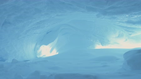 Inside View of Antarctica Ice Cave. White Winter Background. Amazing Polar Landscape. Snow, Ice Covered Glacier Grotto of Antarctic Continent. Harsh Wild Environment. Permafrost. 4k Footage.