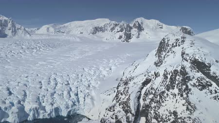 Aerial Flight Over Antarctica Snow Covered Mountains, Polar Ocean. Amazing Drone Overview Of White Winter Landscape. Exotic Travel To Antarctic Wilderness. Beauty Of Virgin Nature. 4k Footage.