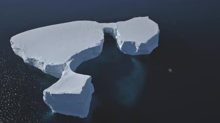 eye piece : Aerial Overview Of Iceberg Among Antarctica Ocean. Drone Flight Over Huge Ice Mountain. Sunlit Cold Ocean Water. Winter Antarctic Landscape. Wilderness. Virgin Nature. 4k Footage.