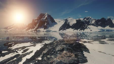 zuidpool : Sunset over Antarctica Mountains, Ocean. Lemaire Channel Aerial Flight. Drone Overview Shot Of Mighty Mounts, Snow, Ice Covered Land. Bright Sun Over Ice Cold Ocean. Winter Landscape. 4k Footage.