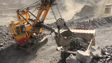 yükleyici : Industrial excavator and working man in a quarry, a large jaded industrial excavator
