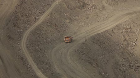 żelazko : A large tipper digs through a career, an industrial truck dredges cargo in its quarry, a large yellow dumper