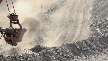 mozdony : A large tipper digs through a career, an industrial truck dredges cargo in its quarry, a large yellow dumper