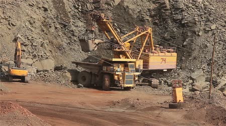 hidrolik : The excavator and dumper in the quarry, Large yellow excavator loaded ore into a dumper Stok Video
