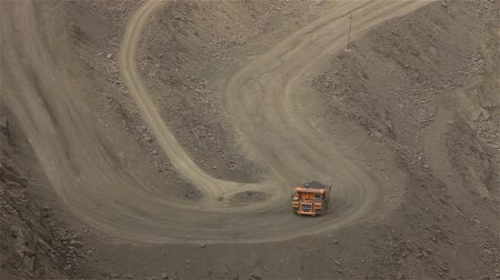 minério : A large tipper digs through a career, an industrial truck dredges cargo in its quarry, a large yellow dumper