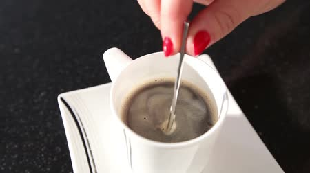 kahve molası : A woman stirs a coffee with a spoon, A girl stirs sugar in a coffee spoon, close-up