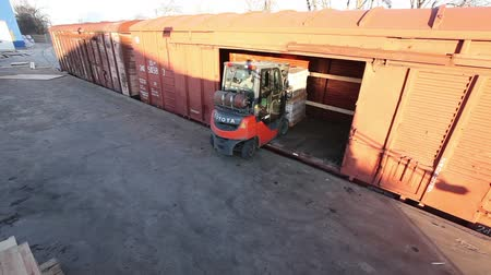 řídit : The loader takes the goods to the train, Loading of goods into a train, Industrial exterior