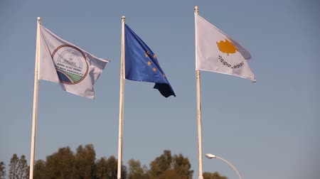 inferior : Flags of the European Union, Greece, Cyprus, the city of Aya Napa, Greece, Flags on the flagpole, the wind waving the flag, Flags on flagpole, wind waving flag, against blue sky background