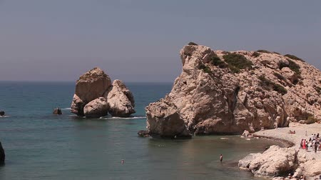 İspanya : People bathe and sunbathe on a small sandy beach, the birthplace of Aphrodite on the island of Cyprus, Rocks stick out of the sea water, Beautiful beach in the Mediterranean Sea, rocky beach Stok Video
