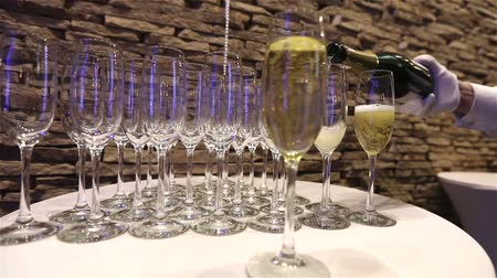 szampan : The waiter pours champagne in wineglass, in a restaurant, The waiter pours champagne in crystal glasses, Restaurant interior, buffet table, Waiter in white gloves, close-up