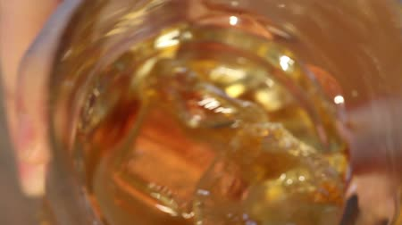 алкоголизм : Pouring scotch whiskey over ice, close up