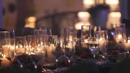 украшенный : Decorative candles on the dining table, glasses and Christmas candles on the table, white wax candleswith glass candlestick, Candle with Glass Candlestick, restaurant, interior, close-up Стоковые видеозаписи