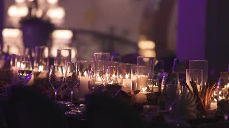 cera : Decorative candles on the dining table, glasses and Christmas candles on the table, white wax candleswith glass candlestick, Candle with Glass Candlestick, restaurant, interior, close-up Stock Footage