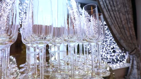 szampan : Glasses on the buffet table, a bottle of champagne, restaurant design, interior, indoors, smooth movement of the camera along the table, rows of wine glasses on the table, shallow depth of field