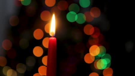 candlestick : Red candle on a dark background, Christmas candle on bokeh lights background, Christmas evening, New Year, xmas, colored circles, bokeh, closeup
