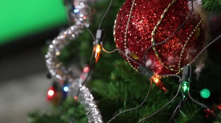 adorno : Christmas tree with toys, a garland electric is on the tree, red christmas ball, close-up