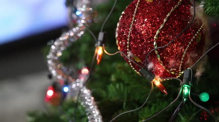 gałązki : Christmas tree with toys, a garland electric is on the tree, red christmas ball, close-up