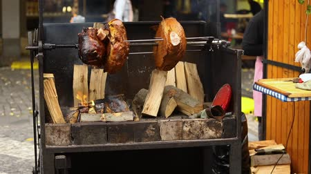 plivat : Large chunks of delicious pork hams cooked on an open fire. The street food. Food outdoors. Camping and cooking on a spit over the fire, man cooks large pieces of meat on a spit on fire, closeup