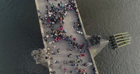 Česká republika : Tourists stroll along the Charles Bridge in Prague, Panoramic view from above, Vltava River, flight over the Charles Bridge, Prague