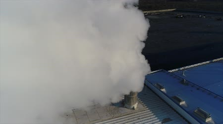 smoke from a pipe on the roof of a factory or factory, the roof of a production room with a pipe, white thick smoke exits the pipe Wideo