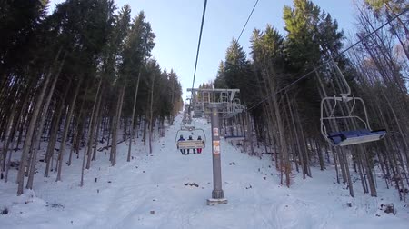 лыжник : a ski lift carries people up on the mountain, Skiers descend from the snowy mountains, people are skiing, high spruces on the hillside, sunny day, from the first person
