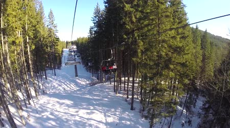 лыжник : A ski lift carries people up on the mountain. Skiers descend from the snowy mountains. People are skiing, high spruces on the hillside, sunny day Стоковые видеозаписи