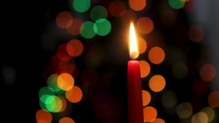 castiçal : Red candle on a dark background, Christmas candle on bokeh lights background, Christmas evening, New Year, xmas, colored circles, bokeh, closeup